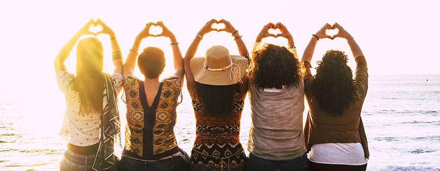 5 women in reflection looking out to the ocean and holding theirs hands in a heart shape.